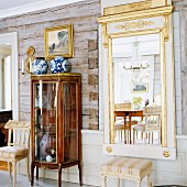 Antique glass display case and gilt-framed mirror on rustic wall of log cabin