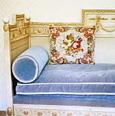 Head end of ornate, neoclassical wooden daybed with light blue velvet upholstery