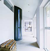 Semicircular protrusion with blue glass strip in corridor with windows along one side