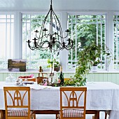 Biedermeier chairs at set table with white tablecloth in front of large window
