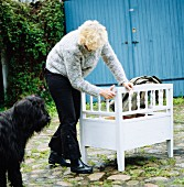 Black dog next to woman in cobbled courtyard repairing a white bench