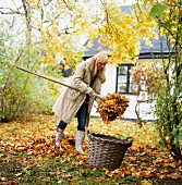 Young woman raking up leaves in autumnal garden