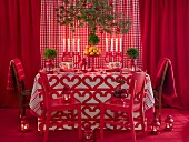 Dining table surrounded by red decor, Plants and candle on it