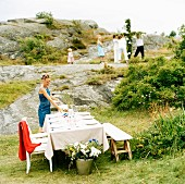 A woman setting the table for midsummer celebrations.