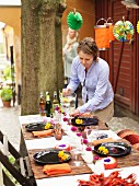 Woman preparing table for traditional cryfish party