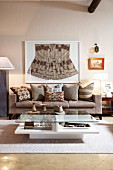Framed, ethnic garment above precisely arranged cushions in ethnic patterns on grey couch in modern living room; wooden collectors' items on coffee table