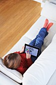 Boy on sofa using digital tablet
