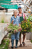 Young woman and mature man walking with hanging baskets in garden centre