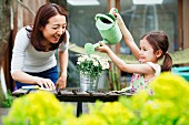 Mother and daughter with toy watering can in garden