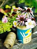 Vintage Dose als Vase für Sonnenhut- und Windröschenblüten auf einem Gartentisch