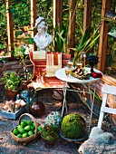 Sitzplatz in Wintergarten mit Birnenkorb, Deko aus Naturmaterialien und Frauenbüste im Hintergrund