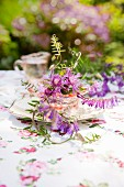 Wild flowers in old glass bowl on vintage plate as centrepiece on table in garden