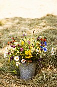 Bouquet of wild flowers in old bucket amongst hay