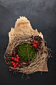 Small wreath of foraged natural items; fragment of wood, moss, twisted dried grasses, elderberries and rosehips on dark metal surface