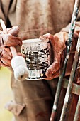 Hands holding can of paint and paintbrush