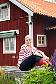 Smiling young woman sitting on wooden balustrade in front of falu red house