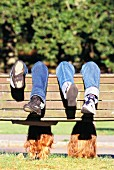 Two girls hanging upside down on wooden bench