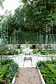 Symmetrically arranged vegetable beds with small, trophy-shaped fountains in background