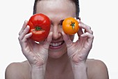 Young woman covering eyes with red and yellow tomato