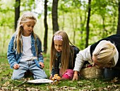 Mother and daughters picking mushrooms in forest