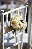Posy of roses tied to chair back