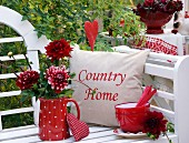 Red dahlias in red, polka-dotted jug next to stack of bowls and cushions on white garden bench