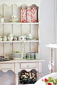 Crockery and ceramic vessels in rustic dresser with open-fronted top