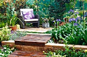 Sunny seating area with comfortable armchair on garden terrace with integrated flower beds