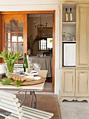 Gedeckter Tisch, im Hintergrund kleiner Kühlschrank im Holzschrank versteckt, auf ländlich möblierter Veranda