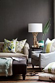 Upholstered seating with scatter cushions and table lamp with white fabric lampshade on natural wood base against wall painted dark brown