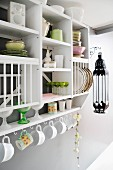 Crockery on open-fronted kitchen shelves and cups hanging from hooks below