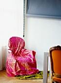 Stuhl mit pinkfarbenem Stoff eingepackt in Zimmerecke