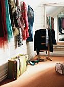 Verschiedene Halstücher an Wandhaken und Vintage Koffer vor stummen Diener am Wandspiegel in holzverkleideter Ankleide