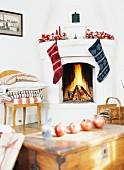 Pomegranates on wooden trunk and open fire in fireplace with Christmas decorations