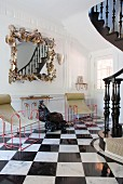 Postmodern, framed mirror and metal chairs with fabric seats in hallway with black and white, chequered marble tiles