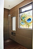 Shower head on wall with large tiles and opaque window with peacock feather motif in shower area