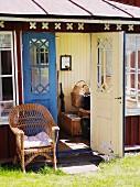 Wicker chair in front of open door of wooden cottage