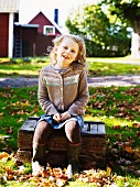 Girl sitting on wooden crate in autumnal garden