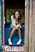 Smiling woman sitting inside outhouse