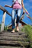 Junge Frau läuft mit Zeitung in der Hand eine vergraute Holztreppe nach unten