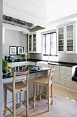 Wooden barstools at counter in white fitted kitchen with black worksurfaces