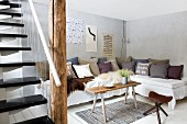 Vintage bench used as coffee table in front of corner sofa with scatter cushions; floating staircase with wire balustrade in foreground