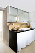 Broad, mirrored cabinet above orange mosaic tiles and black-painted washstand with white curtain