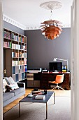Poulson lamp hanging from stucco ceiling rose above modern coffee table; office area in background with antique writing desk and delicate office chair against grey wall