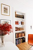 Branches of red flowers in vase next to fitted shelves of antiquarian books and partially visible leather chair