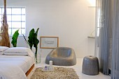 Futon-style double bed and grey designer chair and stool against white wall