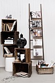 Books and ornaments in stacked wooden crates next to fashion magazines on ladder rungs