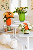 White side tables with bright flower arrangements in vivid green and rich orange