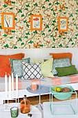 Sitzbank mit Polster und Kissen vor weisser Wandvertäfelung, darüber florales Tapetenmuster mit orangefarben gerahmten Blumenbildern