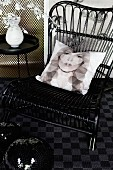 Scatter cushion with print portrait (Kate Moss) on black wicker chair, disco balls and vase on side table